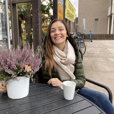Vihreään toppatakkiin ja vaaleaan huiviin pukeutunut nainen istuu kahvilan terassilla edessään kahvikuppi ja syksyinen kukka.