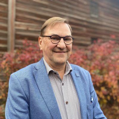Jääkiekon MM-kisojen 2022 pääsihteeri Heikki Hietanen katsoo hymyillen kameraan taustalla ruskan värisiä pensaita sekä punertavaa hirsiseinää. Kuva otettu 8.10.2021.