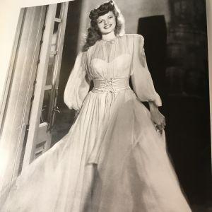 Rita Hayworth i klädd en vit chiffongklänning.