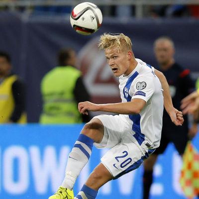 Fotbollspelare håller boll i luften.