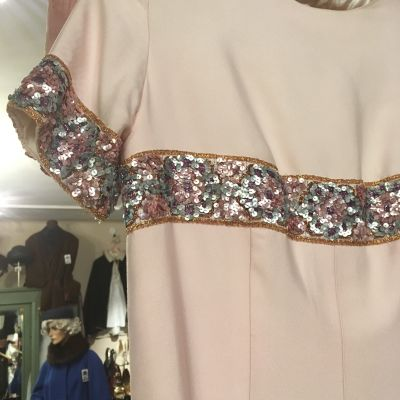 En rosafärgad klänning med paljettdekorationer.