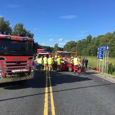 En brandbil som står vid en trafikolycksplats där en bil är kraschad.