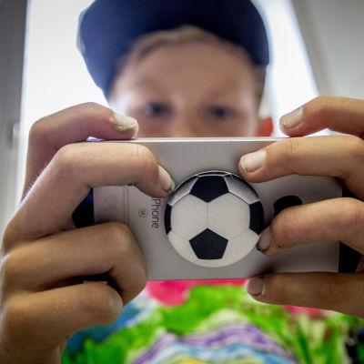 Pojke som spelar på sin mobil.