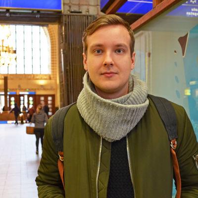 Ville Ritala står i Helsingfors Centralstation, i bakgrunden folk och stora vackra fönster.