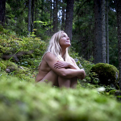 Anne Hietanen utan kläder sittandes på ett mossigt berg.