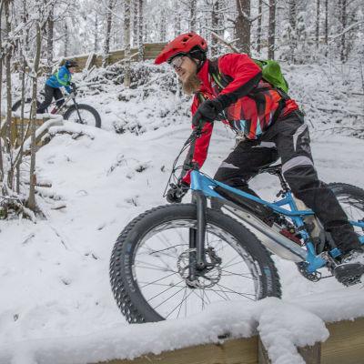 Sami ja Paavo Korhonen ajavat ränniä pitkin lumisessa metsässä.
