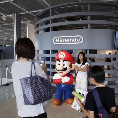 Henkilö asettautuu valokuvattavaksi Super Mariota esittävän mainosnuken viereen.