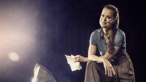 Skådespelaren Emma Klingenberg står på ett scengolv bredvid en grammofonspelare. På golvet ligger gamla papper kringströdda.