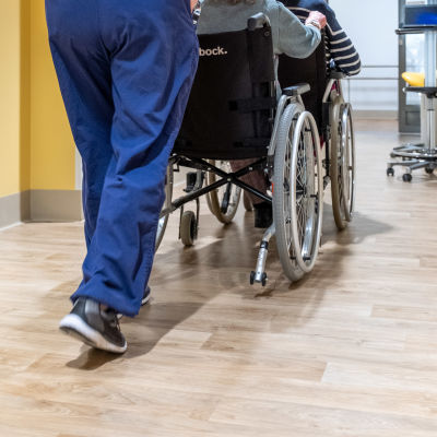 Hoitaja työntää vanhusta pyörätuolissa.