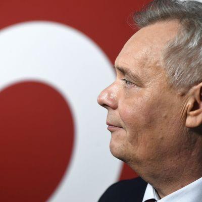Antti Rinne framför en SDP-logga.