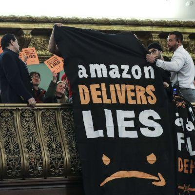 """""""Amazon levererar lögner"""" står det på banderollen som vecklades ut från balkongen under höringen med Amazons ledning i New York Stadshus."""
