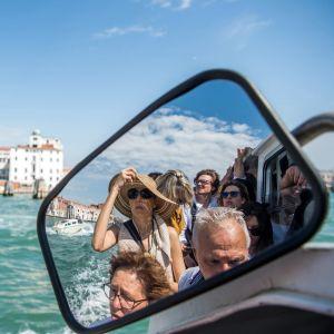 Turister på båtfärd i Venedig.