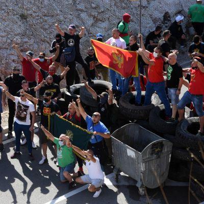 Människor demonstrerar med Monenegros flagga.