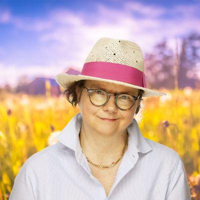 Laura Kolbe ler in i kameran med en stråhatt på huvudet. I bakgrunden syns en sommaräng.