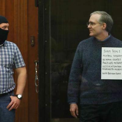 Den spiondömde amerikanen Paul Whelan står bredvid en amskerad rysk vakt