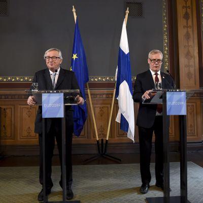 Jean-Claude Juncker och Antti Rinne står brevid varandra i varsin talarstol. Bakom dem syns både Finlands och EUs flagga