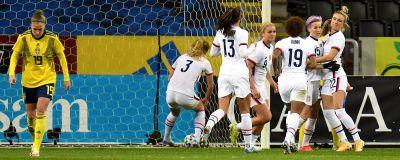 USA:s vitklädda fotbollsdamer jublar i hög efter ett mål medan en ensam svensk spelare deppar.