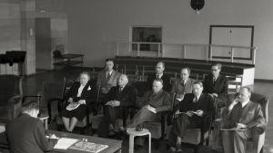 Oy Yleisradio Ab:n varsinainen yhtiökokous Fabianinkadun radiotalossa. Vasemmalta lukien Hella Wuolijoki, tuntematon mieshenkilö, tekninen johtaja Juho Rissanen, tuntematon mieshenkilö ja Markus Rautio. Takarivissä oikealta lukien ensimmäisenä mahdollises