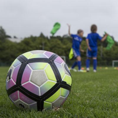 Etualalla värikäs jalkapallo ja taustalla lapsia jalkapallokentällä.