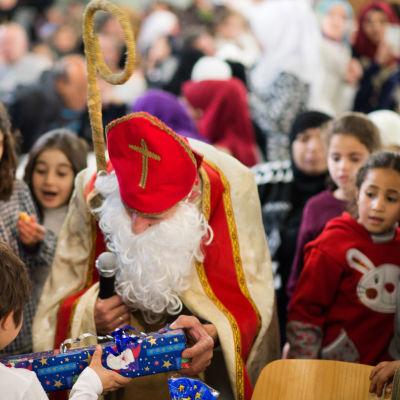 Tysklands version av julgubben St. Nicholas delar ut gåvor till syriska flyktingbarn vid en förläggning i Friedland, Tyskland den andra december 2016.