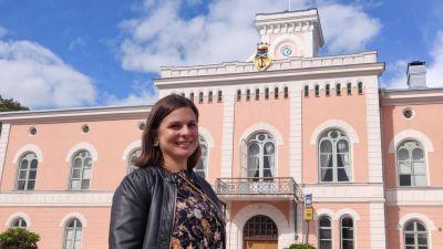 En ung kvinna står framför Lovisa stadshus, ler och ser in i kameran.