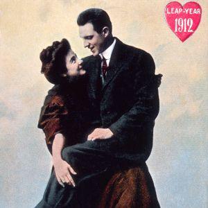 Skottdagskort från 1912. En man sitter i famnen på en kvinna.