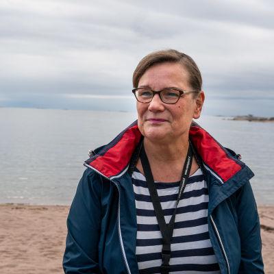 Elisabeth Kajander med havet och sandstrand i bakgrunden.