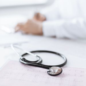 En läkares händer ligger på ett bord. I förgrunden ligger ett stetoskop och ekg-utskrifter.