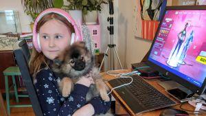 En flicka sitter framför dator med en valp i famnen.