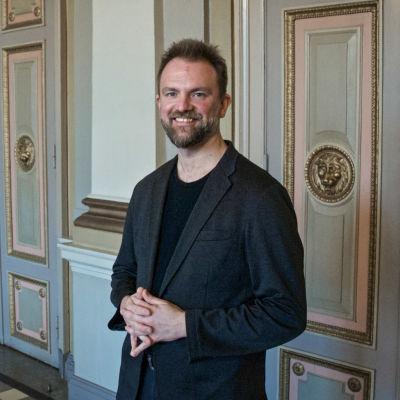 En man står framför utsirade och målade dörrar