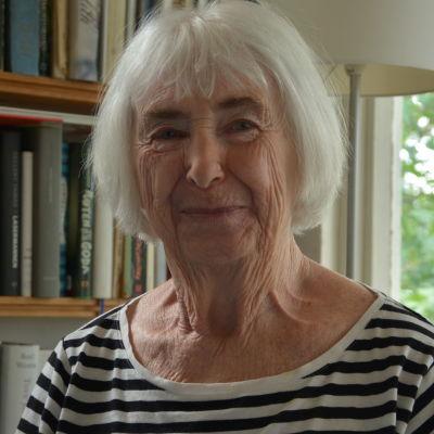 Christina Andersson har på sig en randig skjorta och sitter i en stol framför en bokhylla.