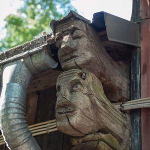 Räystään alle veistetty puuhun kahdet kasvot