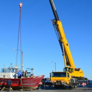 Kranbilen ska lyfta en fiskebåt i vattnet