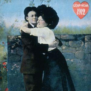 En kvinna kramar hårt om en man. Skottdagskort från år 1912.