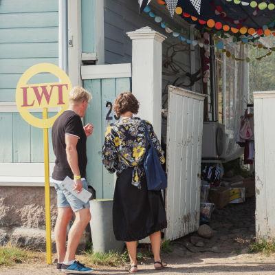 Mies ja nainen ovat menossa puutalon portista sisälle.