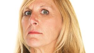 Sträng blond kvinna tittar ogillande in i kameran
