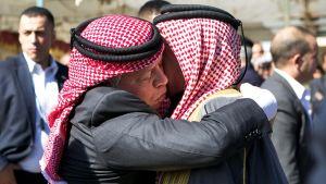 Kung Abdullah av Jordanien (t.v.) omfamnar den mördade piloten Moaz al-Kasasbehs far Safi al-Kasasbeh i dennes hemby Ayr.
