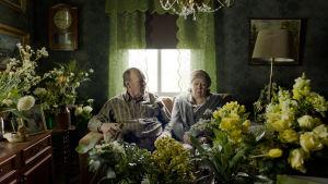 Nisse (Peik Stenberg) och hans syster Elsa (Lena Labart) sitter i en soffa i ett rum fullt med blombuketter.