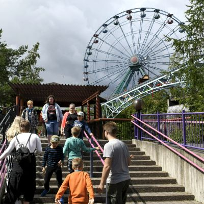 Personer går i trappor på Borgbacken, med ett pariserhjul i bakgrunden.