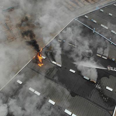 Pelastuslaitos sammuttaa tulipaloa satamahallissa