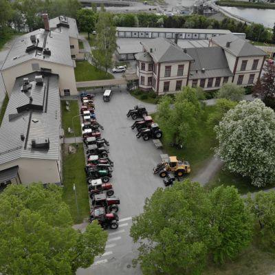 Drönarbild av parkeringen utanför skolavslutningen vid Zachariasskolan år 2021. Ett tjugotal traktorer stod uppradade på en prydlig rad.