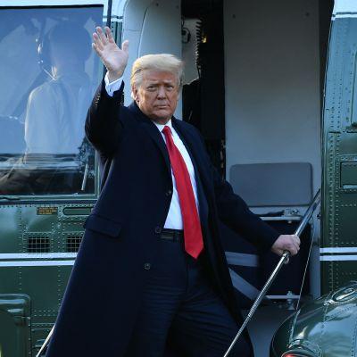 Donald Trump vinkar på väg in i en helikopter.