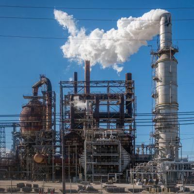 Ett oljeraffinaderi. Rök kommer ut ur en skorsten.