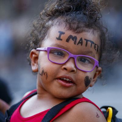 """Tummaihoisen lapsen otsassa lukee englanniksi """"Minulla on merkitys""""."""