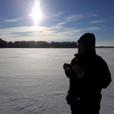 Mies juo kuumaa mehua järven jäällä kovassa pakkasessa.