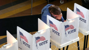 En person med ett barn står i ett röstningsbås i Kalifornien, USA.
