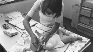Kätilö (terveydenhoitaja) mittaa vauvan päänympärystä.