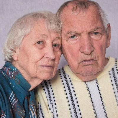 Ett äldre par i blå och gul blus. Det har lutat sina huvuden mot varaandra och ser ledsna eller bekymrade ut i sina ansikten