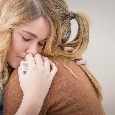 två kvinnliga vänner kramar och tröstar varandra.