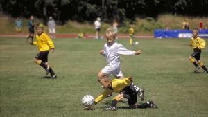 Två småpojkar spelar fotboll.